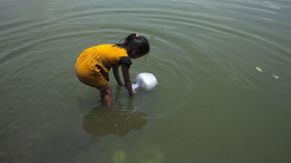 Ein Kind in Bangladesch spielt im Wasser