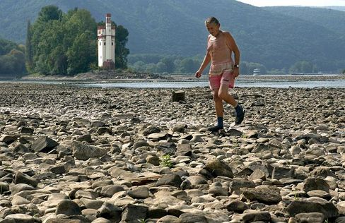 Fußgänger im ausgetrockneten Rhein-Flussbett bei Bingen, August 2003: Die Hitzewelle soll europaweit 70.000 Todesopfer gefordert haben