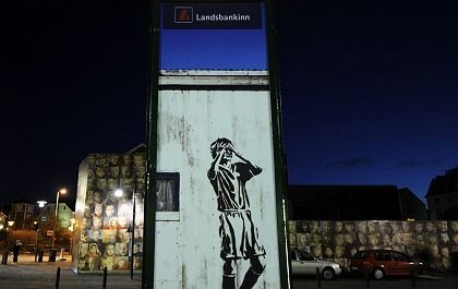 A drawing shows a man holding his head under an advertisement of Icelandic bank Landsbanki.