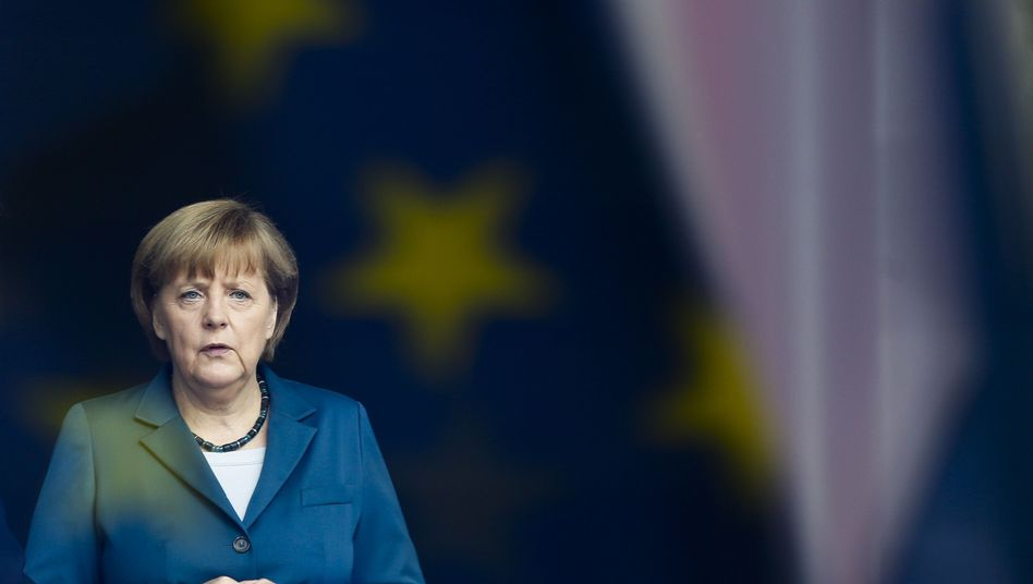 German Chancellor Angela Merkel stands behind a window with the reflection of an EU flag on Monday, June 3.