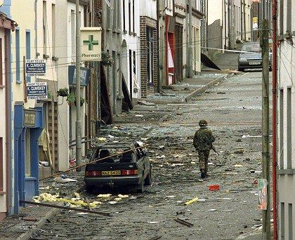 A British soldier walks past the wreckage of a car that contained a bomb in Newtonhamilton in this June 1998 file photo.