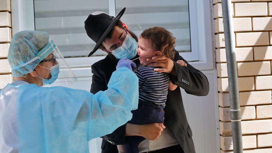 Eine medizinische Mitarbeiterin nimmt in der zentralisraelischen Stadt Cholon einen Abstrich von einem Kind
