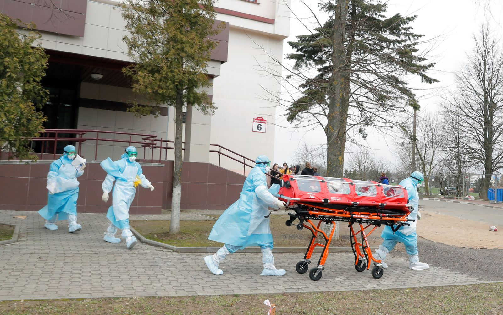 Medical employees wearing protective suits carry capsule with a woman as a measure to fight against the coronavirus contagion (COVID-19)