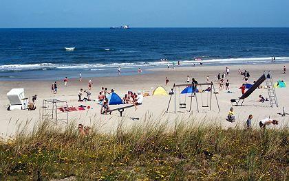 Spielplatz am Strand: Kutter und Containerschiffe ziehen langsam an der Insel vorbei