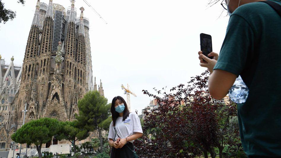 Eine Frau steht vor der Sagrada Família in Barcelona