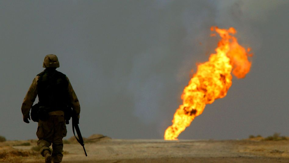 A US soldier walks towards a burning oil well in Iraq's vast Rumaila oil fields in this March 2003 photo: Even directly after the invasion, the US troops didn't pay close attention to the issue of oil.