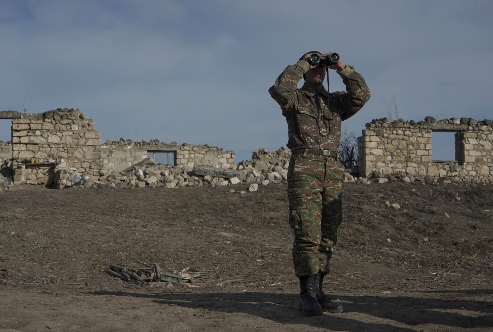 FILE PHOTO: An ethnic Armenian soldier looks through binoculars as he stands at fighting positions near divided Taghavard village in Nagorno-Karabakh region