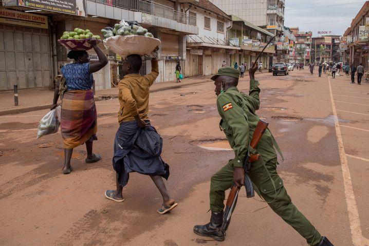 Obstverkäuferinnen in Kampala werden von einem Polizisten geschlagen