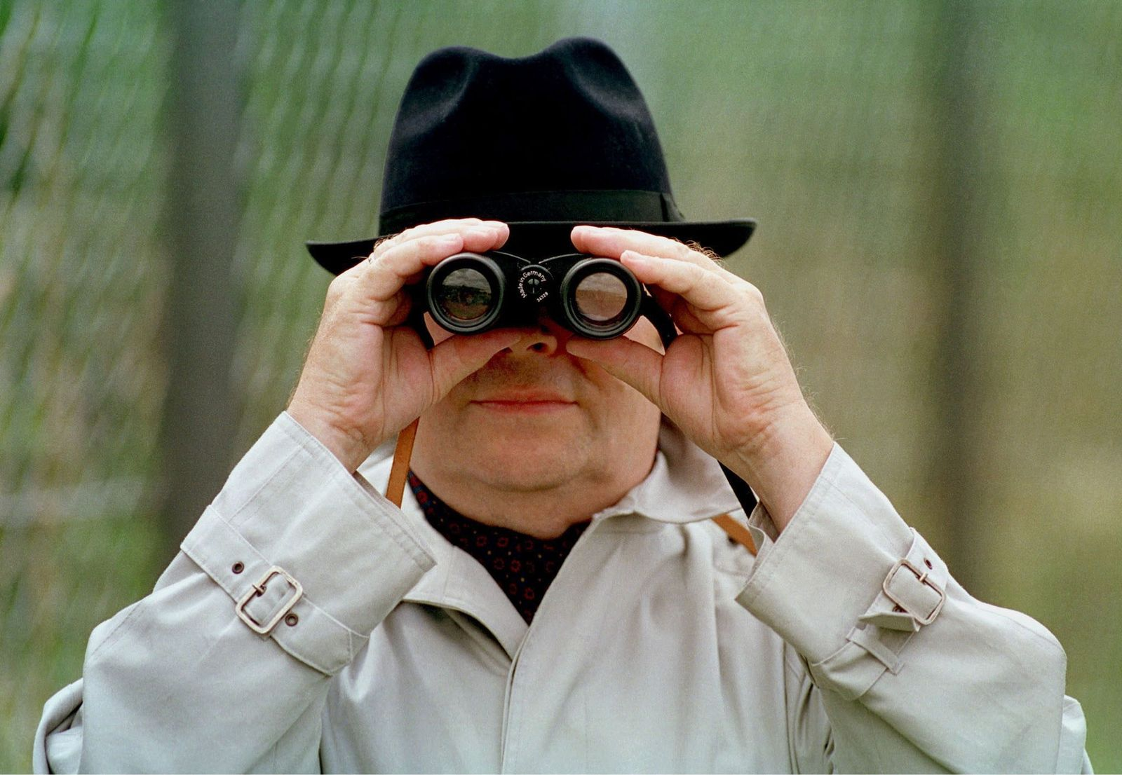 EINMALIGE VERWENDUNG Geheimdienstmythen - Man looks through binoculars, Symbolic photo to the topic: Economic and Industrial Espionage.