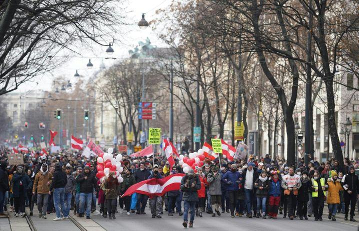 Menschen gehen über die Wiener Ringstraße, um gegen die Corona-Maßnahmen der Bundesregierung zu protestieren.