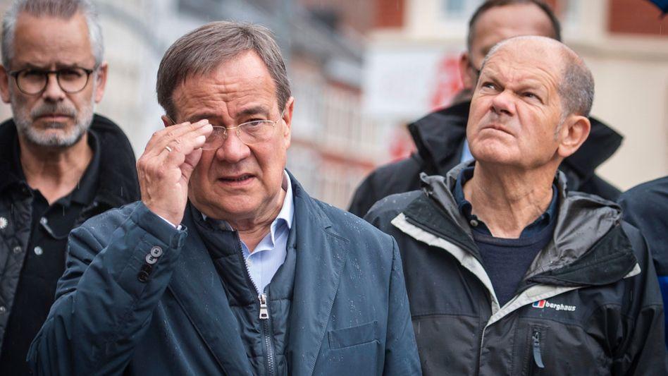 Skeptische Blicke: CDU-Kanzlerkandidat Armin Laschet (2.v.l) und SPD-Kanzlerkandidat Olaf Scholz im von der Flutkatastrophe betroffenen Gebiet