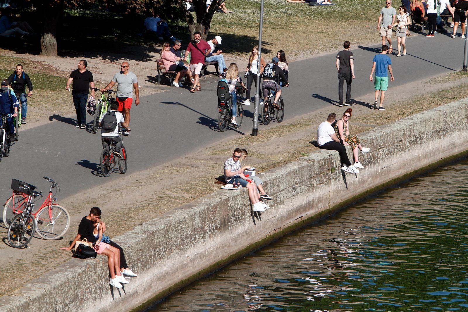 Passanten genießen den warmen Frühlingstag und den Sonnenschein bei einem Spaziergang auf der Uferpromenade am Main in F
