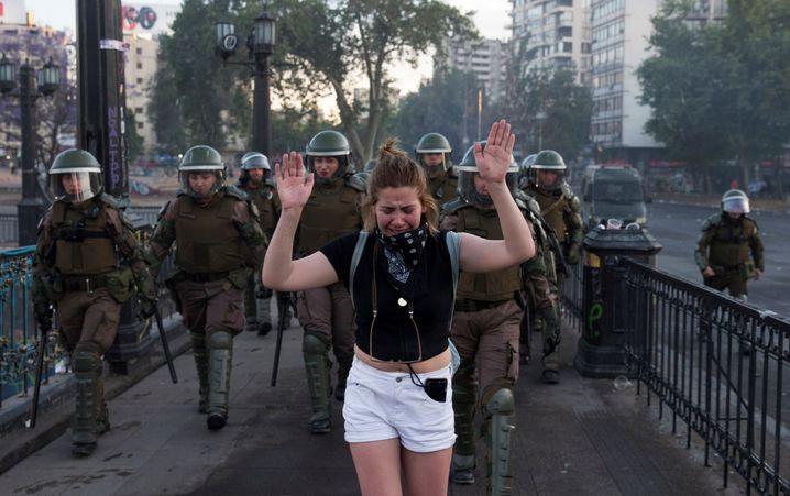 Weinende Demonstrantin und Polizisten in Santiago