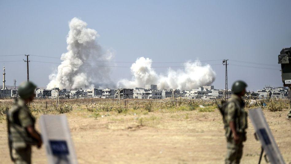 Türkische Soldaten an der syrischen Grenze: Hinter ihnen steigt Rauch über Kobane auf