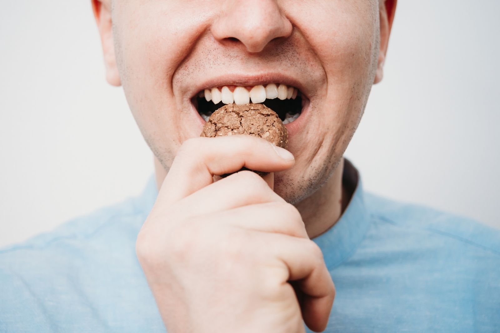 Close-Up Of Man Eating Cookie Against White Background