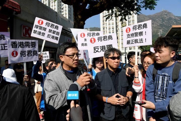"""Junius Ho, umstrittener Kandidat des Regierungslagers spricht an einem Wahlkampfstand mit Passanten: """"Jeder hat seine guten und schlechten Seiten"""""""