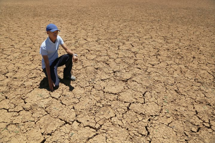 Ein Bauer in Südafrika in einem ausgedörrten Wasserbecken
