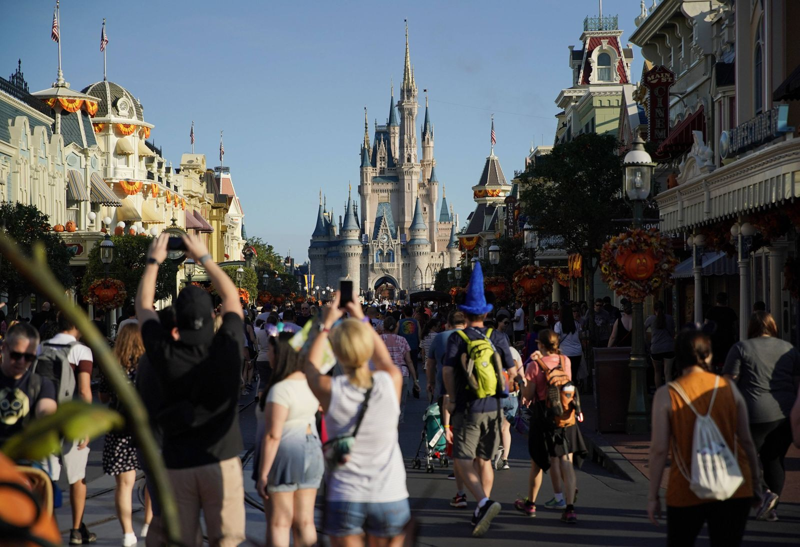 Guests walk near the Magic Kingdom castle at the Walt Disney World theme park and resort on Monday, October 29, 2019 in