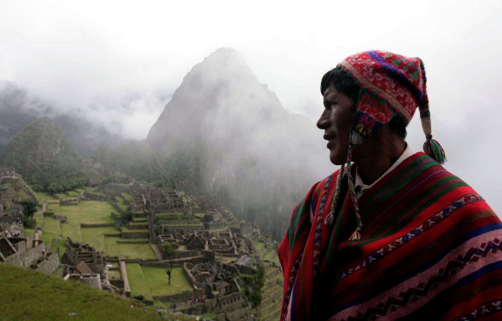 FILE PHOTO: A Quechua musicians stands next to Machu Picchu ruins