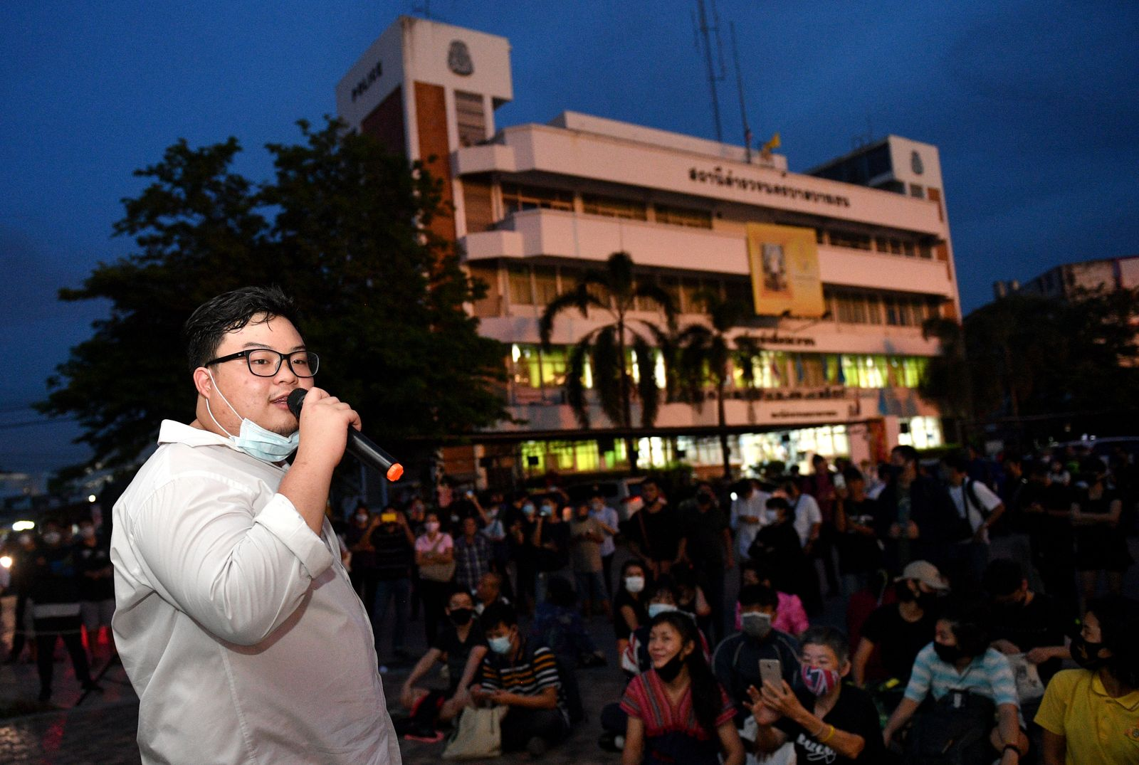Parit Chiwarak speaks to supporters outside a police station where fellow protester Anon Nampa was arrested in Bangkok
