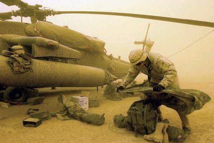 """Nachschub im Sandsturm: Ein US-Soldat belädt einen """"Blackhawk""""-Hubschrauber mit Material"""