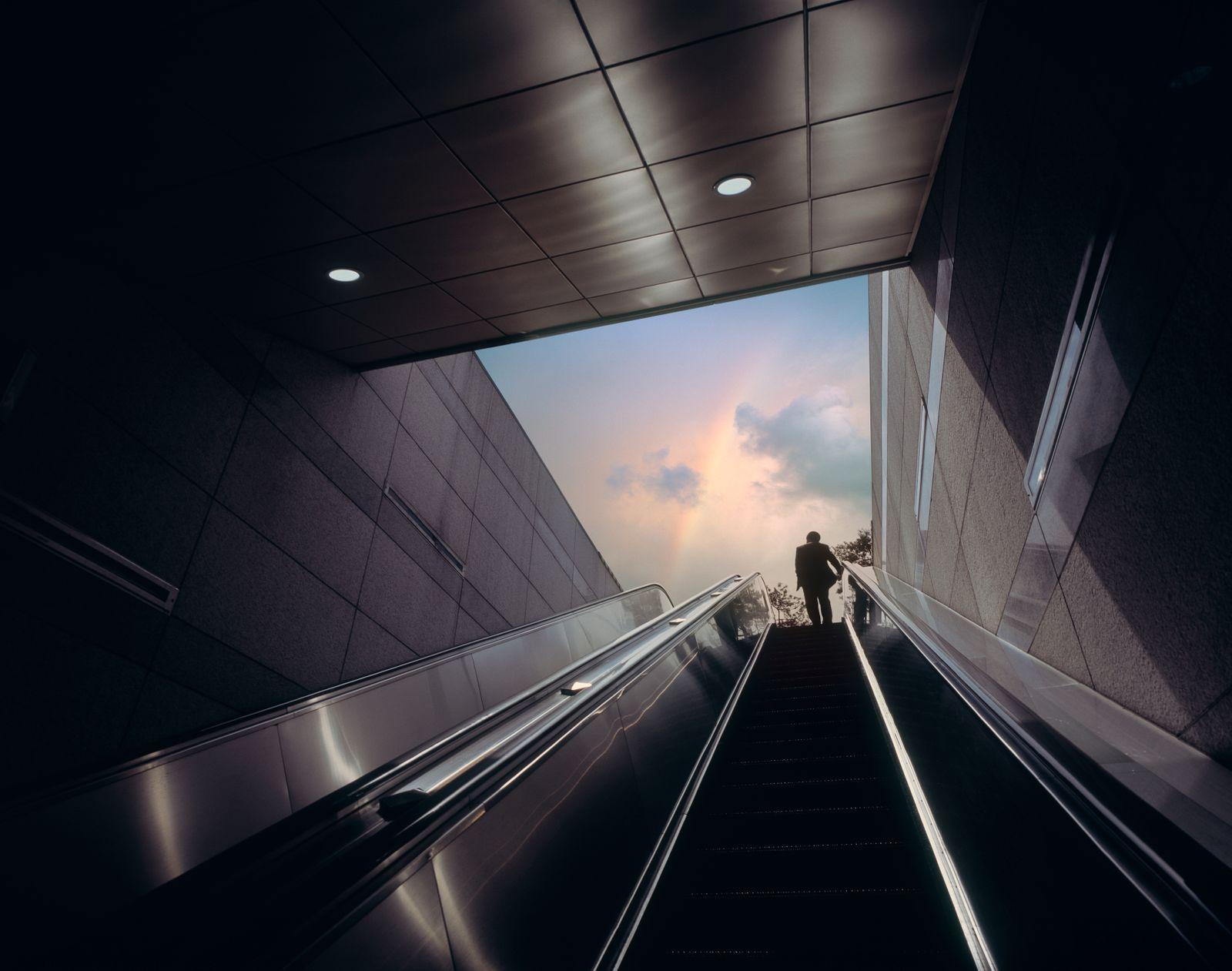 Businessman on escalator moving towards sky with rainbow