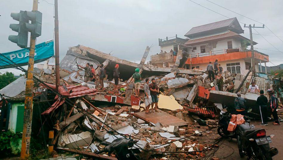 Anwohner inspizieren die Schäden durch das Erdbeben auf Mamuju, Indonesien