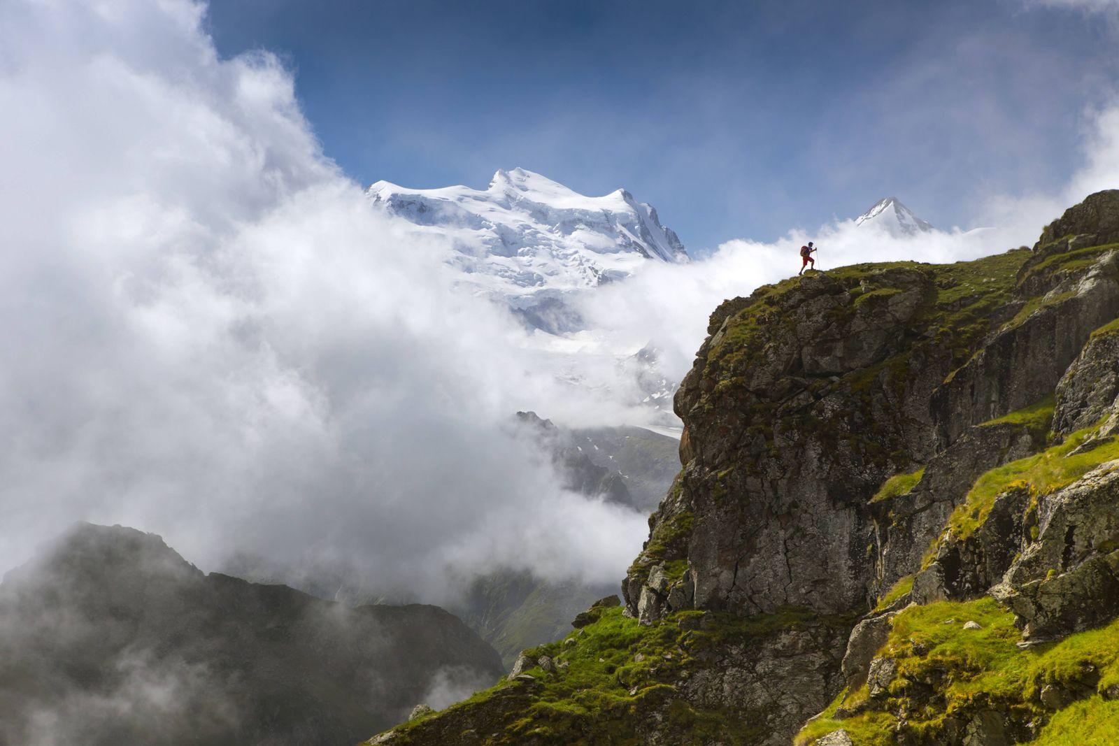 Hiker walking up steep ridge with mountain range in background Haute Route Wallis Switzerland model
