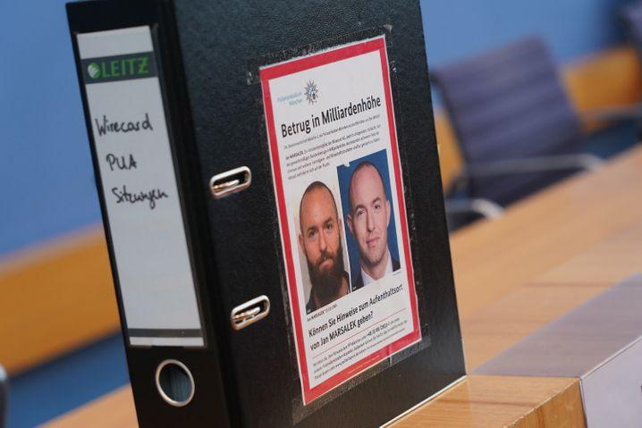 Das Fahndungsplakat des flüchtigen Wirecard-Vorstands Jan Marsalek klebt auf einem Aktenordner des Linkenpolitikers Fabio de Masi