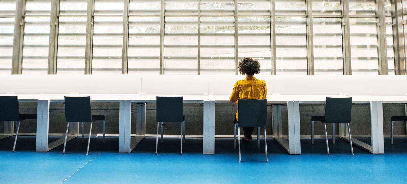 Rear view of young student or businesswoman sitting on desk in room in a library.