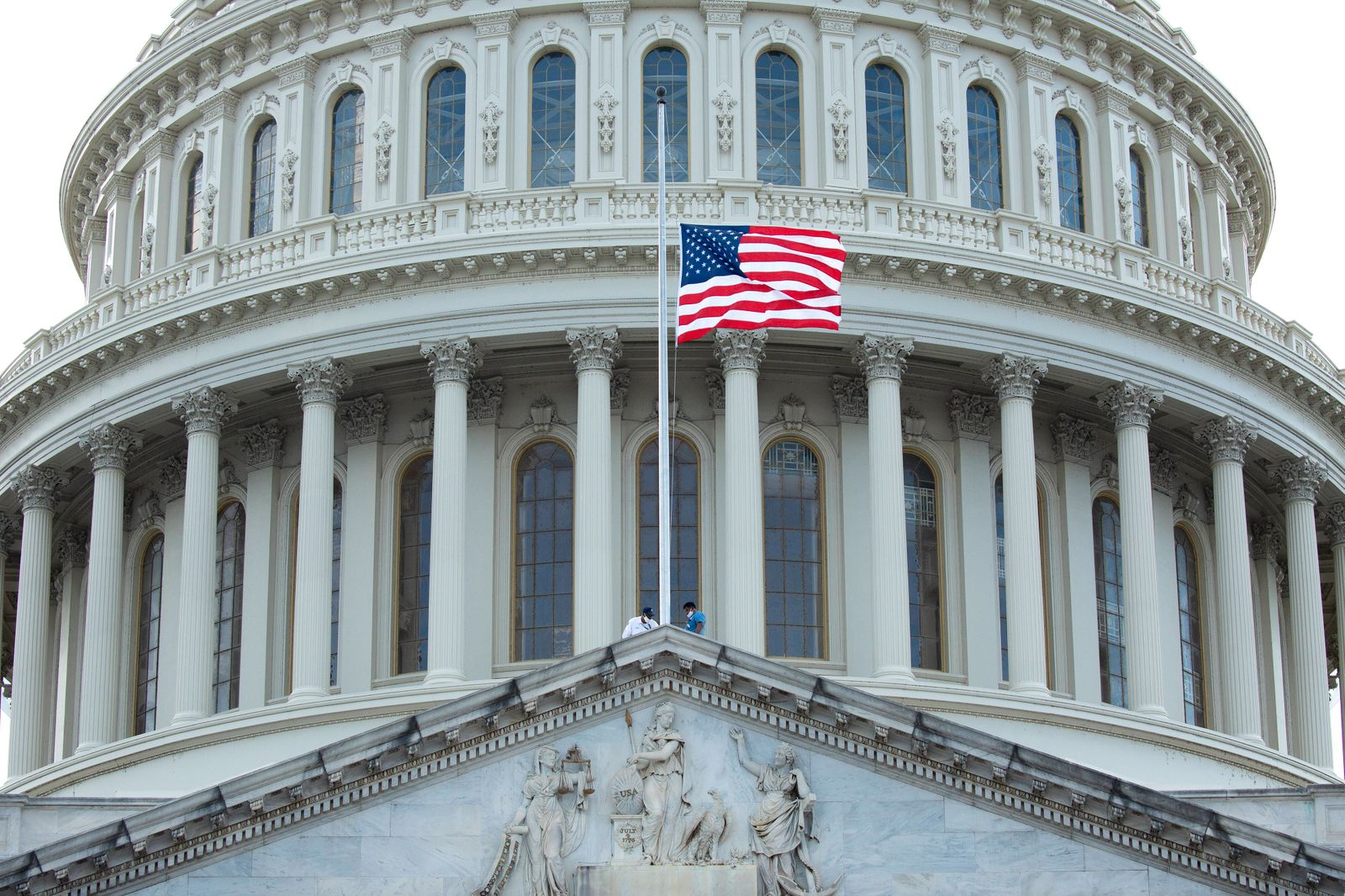 Workers replace the American flag on the U.S. Capitol in Washington D.C., U.S., on Monday, July 27, 2020 as Representat