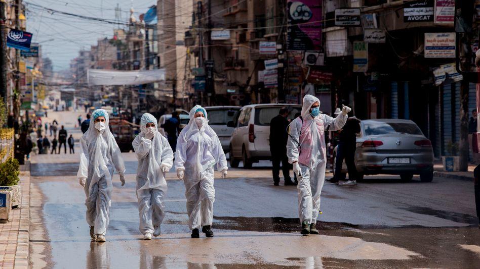 Gesundheitsmitarbeiter überwachen die Desinfizierung von Straßen einer syrischen Stadt