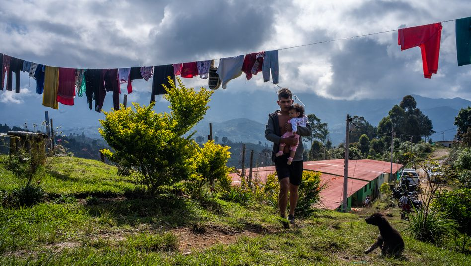 An ex-FARC fighter walks through the camp with his baby.