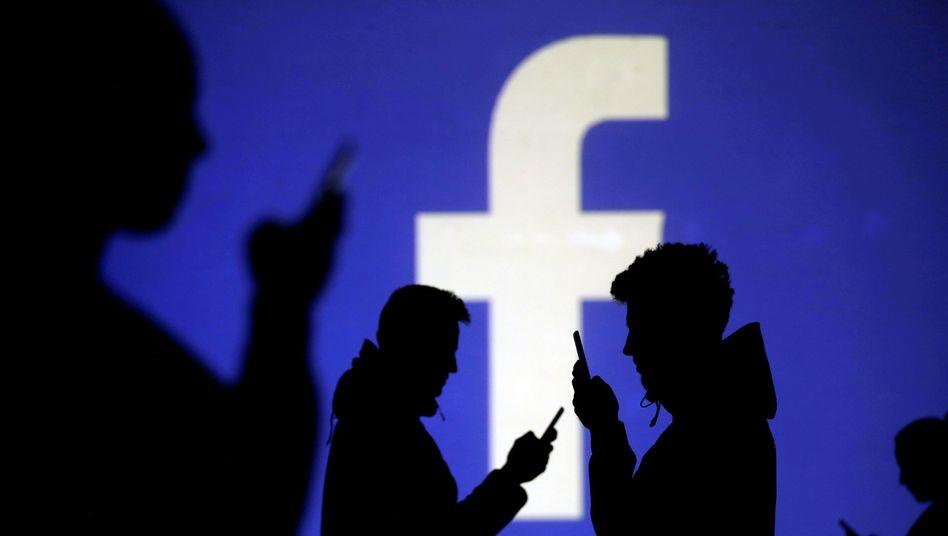 Mobilnutzer vor Facebook-Logo