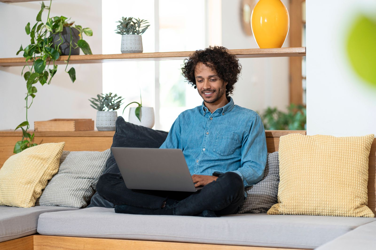 Businessman using laptop while sitting cross legged on sofa at home model released Symbolfoto property released SBOF0378