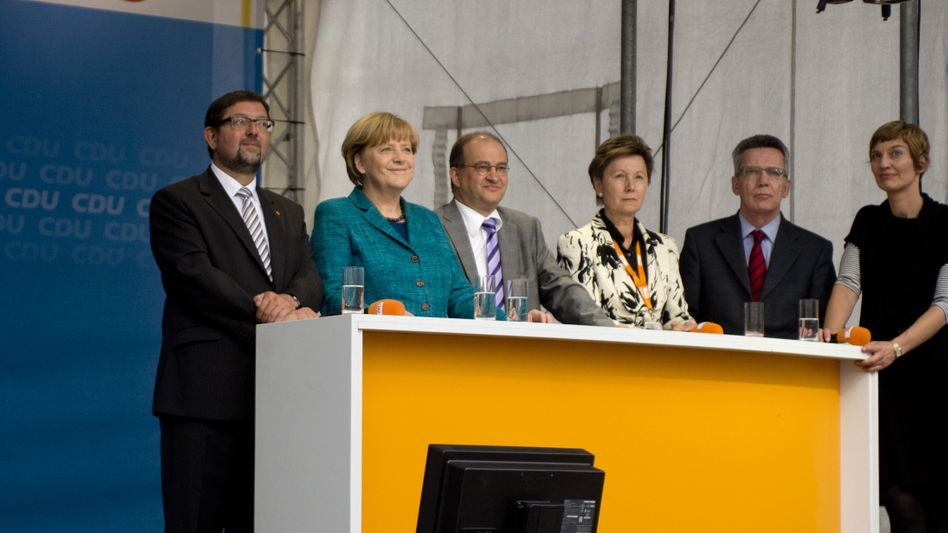 Chancellor Merkel looked on with amusement on Sunday as a miniature drone approaches the stage. Defense Minister De Maizière, right, seemed less pleased.