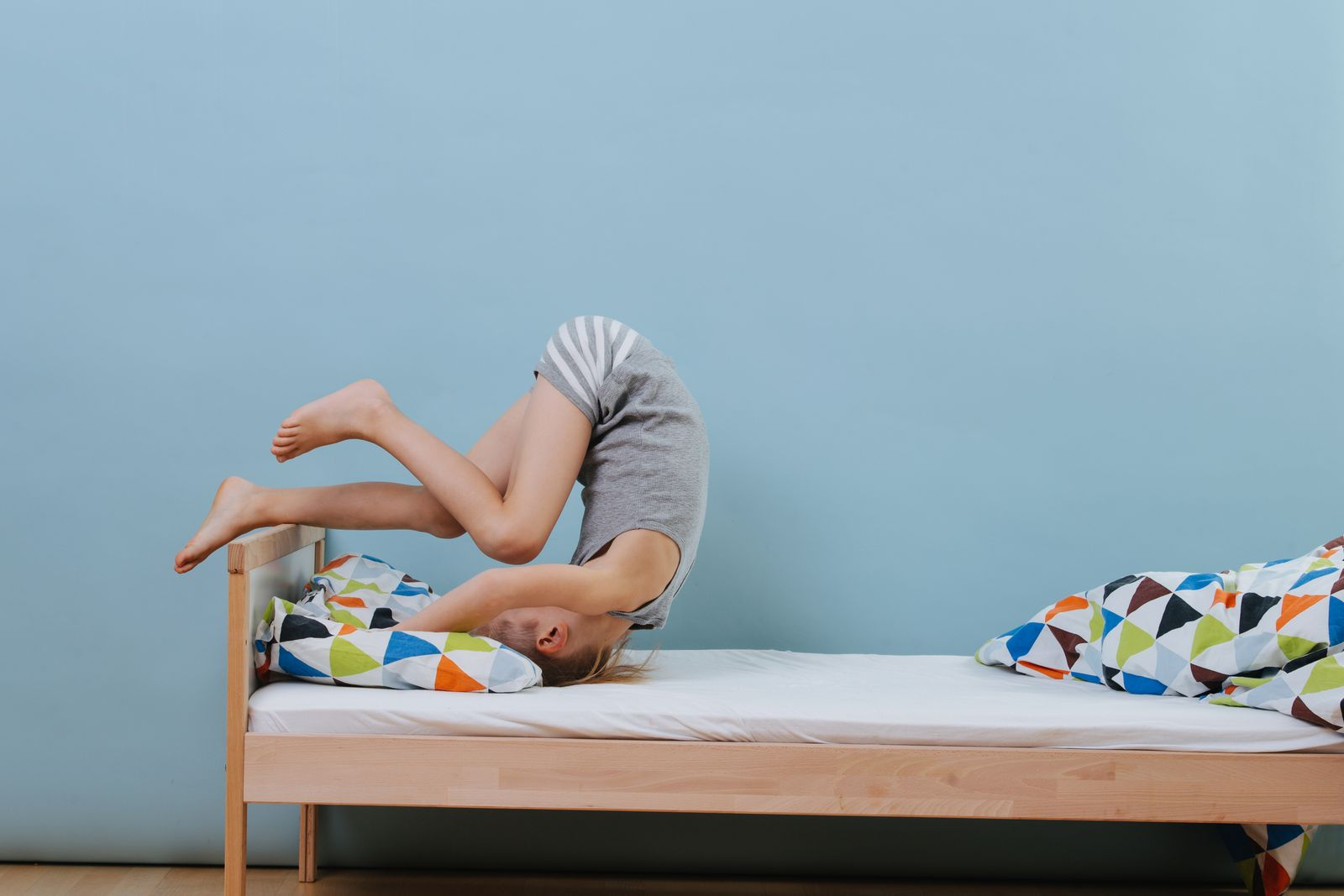 Little boy doing morning gymnastics in unmade bed. Forward roll exercise.