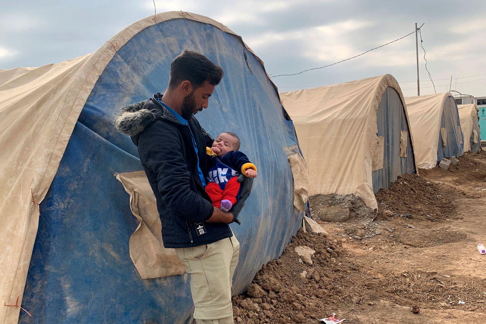 Taama al-Owais, carries his 3-month-old son as he stands in front of his tent in an informal camp in the town of Balad