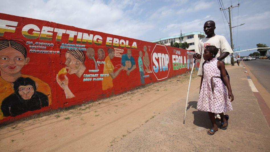Liberia: Ein Mädchen führt seinen erblindeten Vater. Augenschäden und chronische Schmerzen sind die häufigsten Nachwirkungen der aktuellen Epidemie
