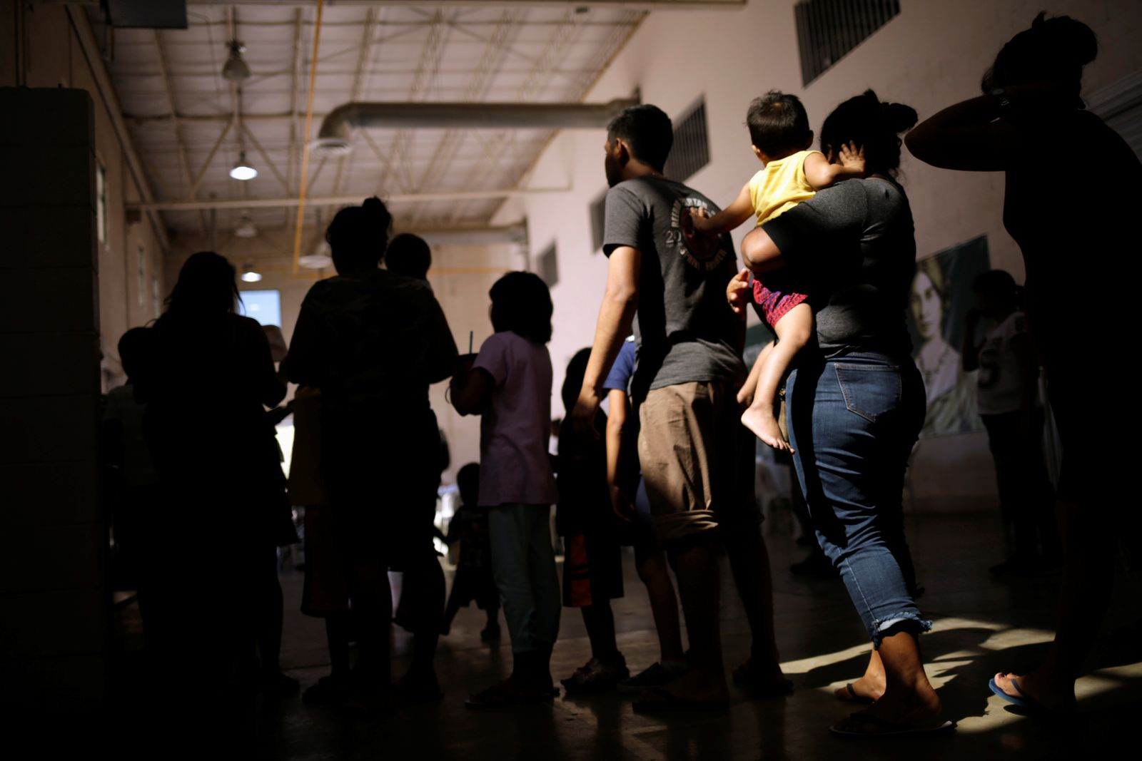 Migrants who returned to Mexico from the U.S. under the Migrant Protection Protocols, line up to receive food at a migrant shelter run by the federal government in Ciudad Juarez