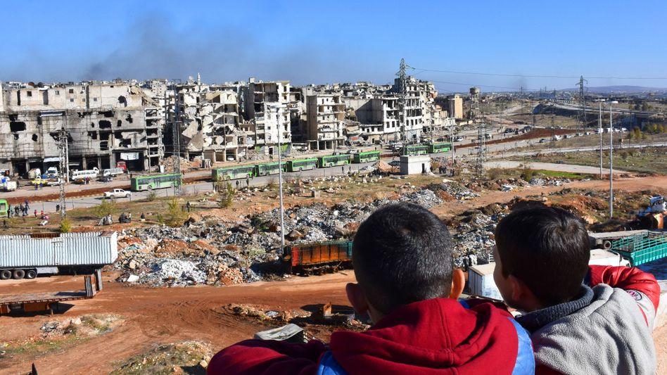 Kinder blicken auf den Evakuierungskonvoi im zerstörten Aleppo