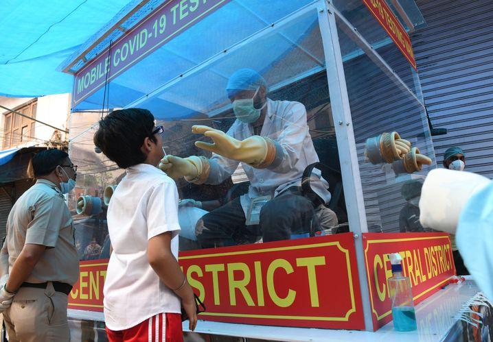 Medizinisches Personal sitzt in Neu-Delhi auf einem Wagen und macht Abstriche für Corona-Tests