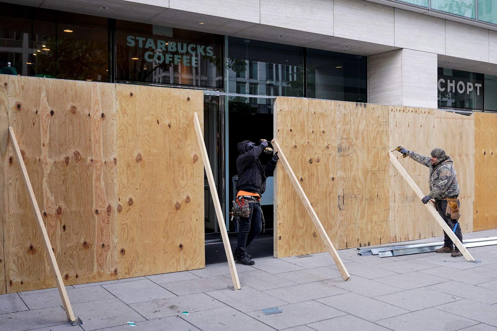 Workers place plywood over storefronts ahead of Election Day near the White House in Washington