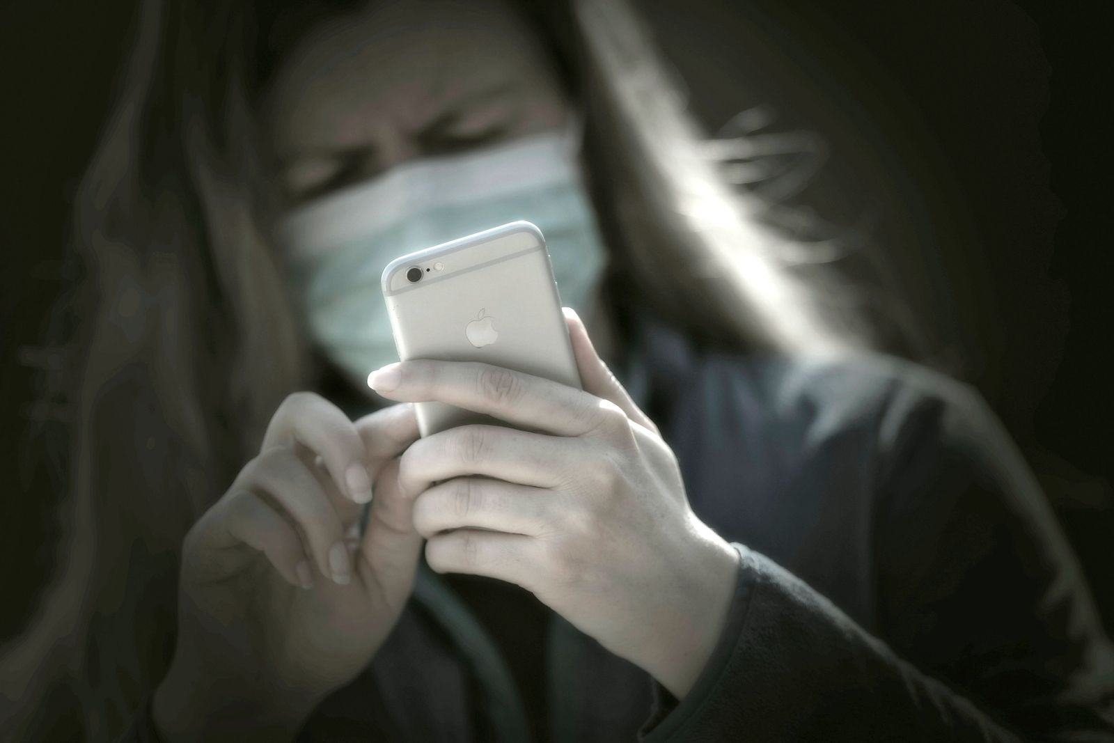 08.04.2020, Symbolbild, Corona-Krise, Frau schaut auf ihr Handy mit Gesichtsmaske. 08.04.2020, Corona-Krise Handy-Nutzu