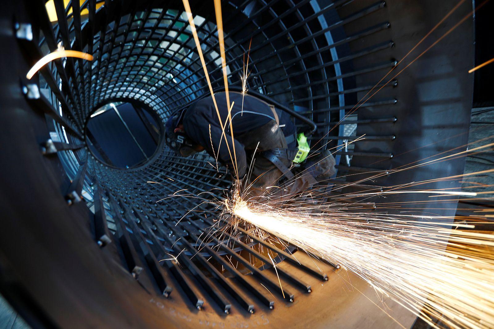 A worker grinds metal at the machine-building company Zemmler Siebanlagen in Massen