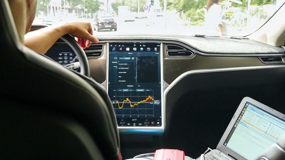 Prüfer der Stiftung Warentest analysieren den Datenstrom der App in einem Tesla