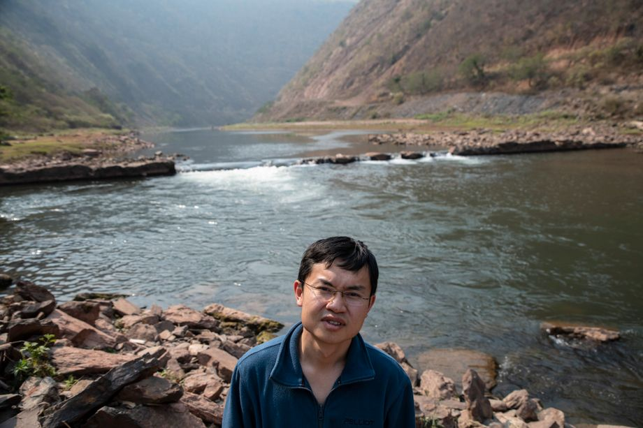 Biologist Gu Bojian on the Red River, with the remains of the planned dam behind him.
