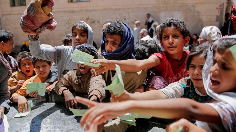 Kinder zeigen in Jemen ihre Dokumente, um eine Essensration zu erhalten (2017)