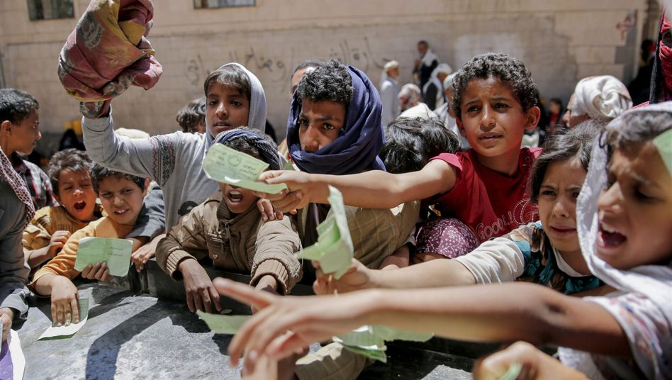 Children in Sanaa receiving food from a local aid organization