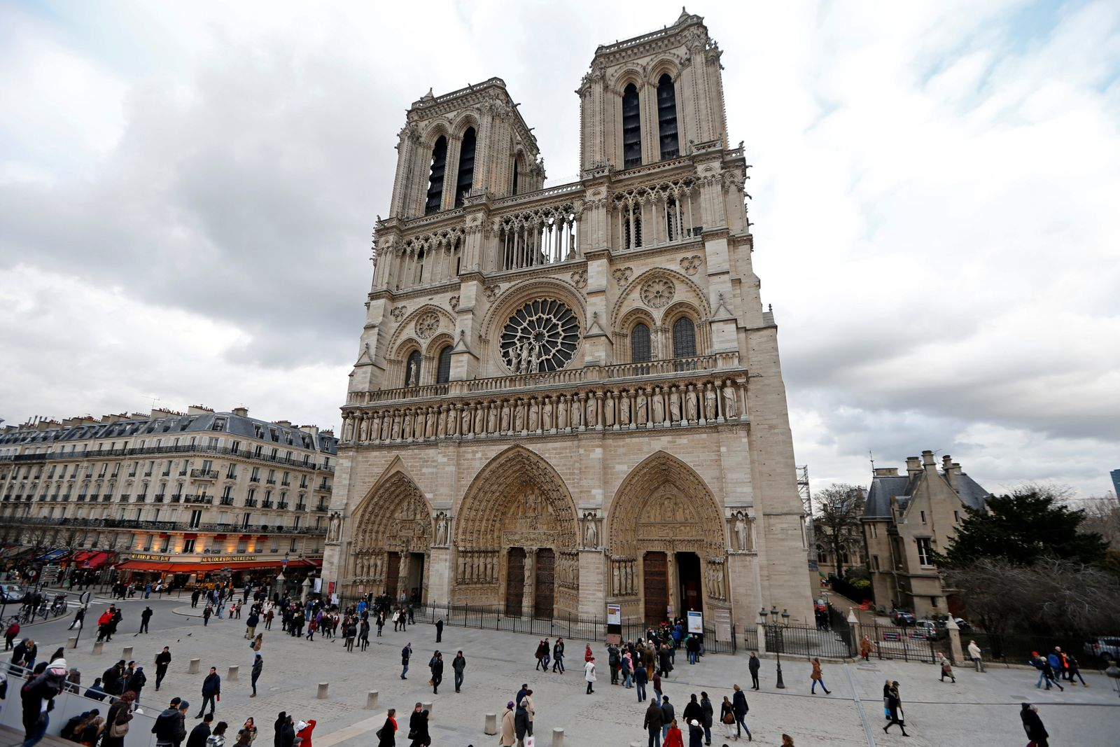 FILE PHOTO: People walk past the entrance to the Notre Dame Cathedral in Paris